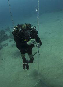 A Mine Clearance Diver attaches detonation cord to a moored mine
